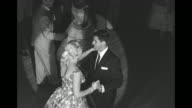 WS people mingling at event inside Brown's Hotel in the Catskill Mountains / comedian Jerry Lewis dances with blonde woman / montage couple performs...