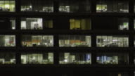T/L MS ZO People moving around and lights turning on and off inside office building at night/ Sydney, Australia