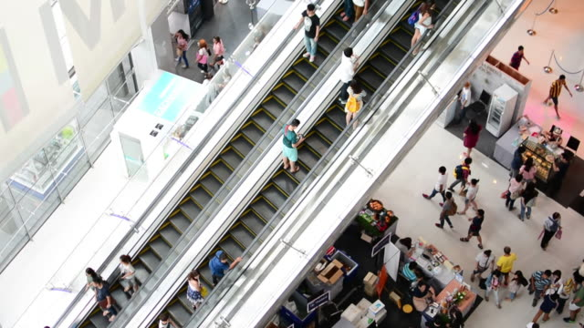 People moving on escalator in shopping mall.