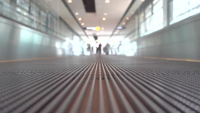 Personen, die auf flache Rolltreppen im Flughafen