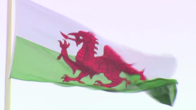 People of Wales remember Charles and Diana's first royal tour Carenarvon Welsh flag flying in wind Wide shot Caernarvon Castle