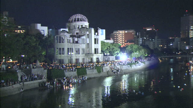People on bank of Motoyasu River release coloured lanterns in annual ceremony in memory of dead at illuminated Hiroshima Peace Memorial (Genbaku Dome)
