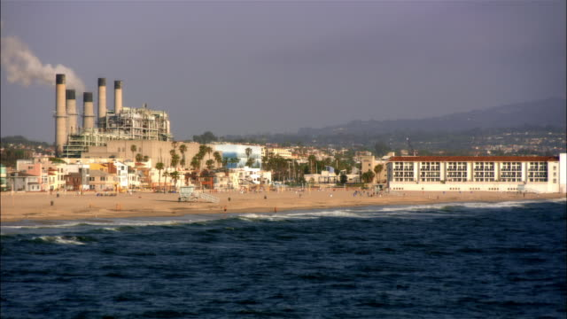WS, People on beach, power plant in background, view from water, Hermosa Beach, California, USA