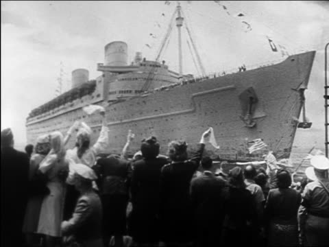 B/W 1945 people on shore waving to military ship as it enters port / WW II homecoming / documentary