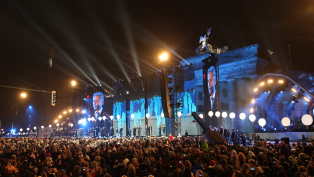 People on the crowd hold their smart phones to record the speech of the then Mayor of Berlin Klaus Wowereit projected on big screen at the back of...