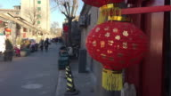 People pass by a lantern during Chinese Lantern Festival in Hutong Alley on Feb 9 2017 in Beijing China