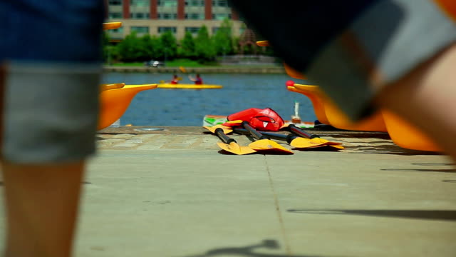 People passing by against yellow kayaks on river