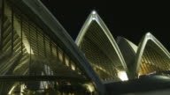 T/L MS PAN People passing up and down steps at Sydney Opera House as others eat at restaurant inside building/ Sydney, Australia