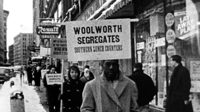 People picketing outside of Woolworth store / Civil Rights activists carrying signs that say 'Woolworth Segregates' / lunch counter protest / white...