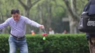 People play with chinese yoyos are seen in Fuxin Park in Shanghai China on Sunday April 10 A man plays with a chinese yoyo around his hips A man...