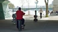 People practicing outdoor sport under Grenelle bridge near Statue Of Liberty of Paris