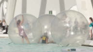 People practising water activities inside plastic balloons that float in a pool
