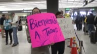 People protest and welcome arriving passengers at Dulles International Airport in Virginia on January 31 2017 The protest follows the executive order...