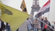 People protesting in Paris in Trocadero with Eiffel Tower visible in background They are protesting against AlSisi egyptian president A woman wears...