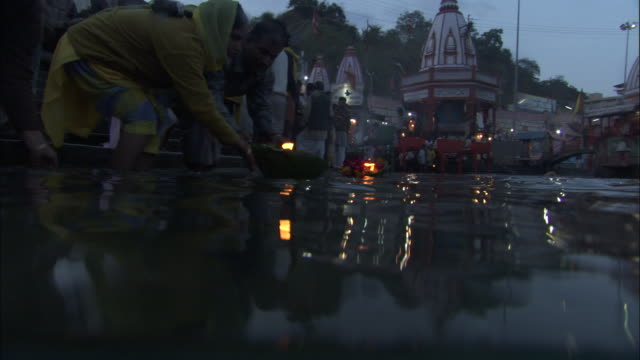 People push lit devotional boats down river as part of Ganga Aarti festival, Haridwar Available in HD.