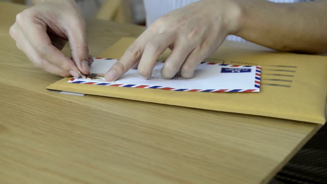 CNGLOTH97 - People putting stamps on letter and package