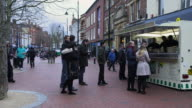 People queue for wraps at a street stand on Broad Street in Reading, UK.