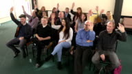 People raising hands in meeting - CRANE HD
