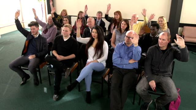 People raising hands in meeting - CRANE HD