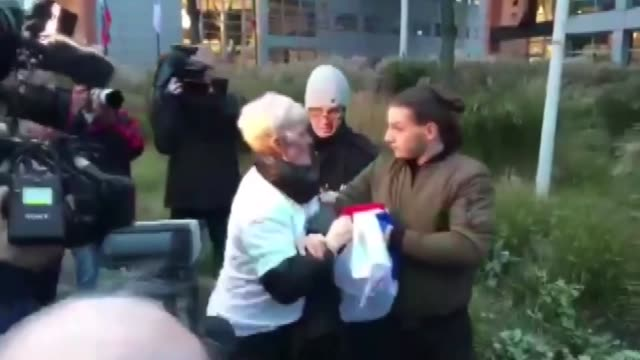 People react to a man who holds Serbian flag as protesters stand outside a court before former Bosnian Serb commander Ratko Mladic appears for the...