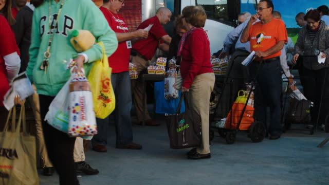 People receiving food and standing in line some having waited in line since yesterday to receive their Holiday Food Baskets outside the Little Havana...