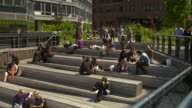 People relax and sit on a set of steps in the Highline park in New York City.