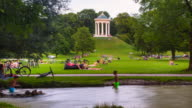 TL People relaxing at Eisbach river in front of Monopteros in the English Garden in Munich
