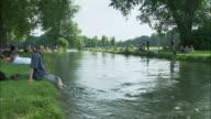 WS People relaxing by river in Englischer Garten (English Garden), Munich, Bavaria, Germany