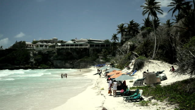 WS People relaxing on beach, The Crane hotel in background / Crane, St Phillip, Barbados