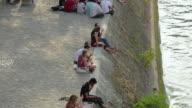 WS TU People relaxing on riverbank, Quai de Bourbon, Ile Saint-Louis, Paris, France