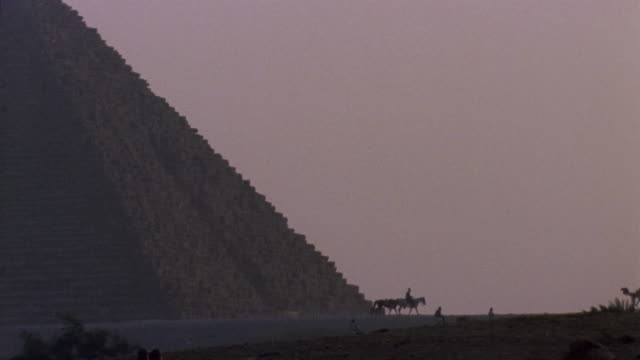 WS People riding horse and camel near ancient pyramid / Giza, Egypt