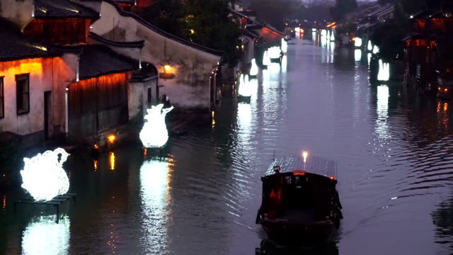 people rowing boat in river of traditional chinese water village.