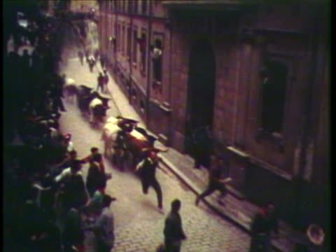 1953 WS PAN People run with the bulls through narrow street and into arena / Pamplona, Spain / AUDIO