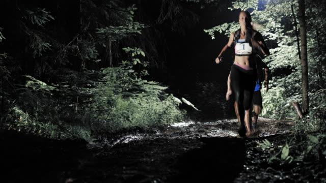 LD persone corsa per la maratona attraverso la foresta di notte