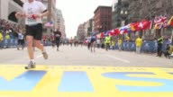 / people running across the Boston Marathon finish line prior to the bombing