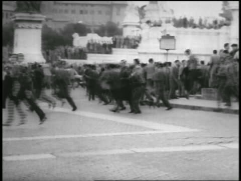 B/W 1956 people running in street in riot / military offroad vehicle driving past / Rome / newsreel
