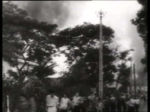 B/W people running past camera with smoke above trees in background / 1960's / Saigon / NO