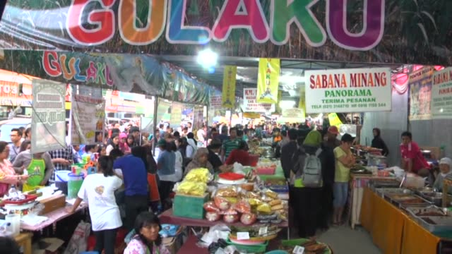 People rush to buy food to break their daylong Ramadan fast at a local food market in Jakarta Indonesia on June 22 2015 Vendors sell food items for...