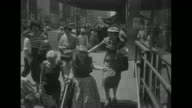 People rush to descend steps into subway station in Manhattan New York City after air raid siren signals civil defense drill / police officer herds...