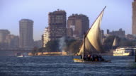 People sail in a traditional dhow along the waterfront of Cairo.