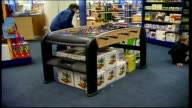People shopping for toys ENGLAND Birmingham INT GV woman at cash counter as paying for goods / GVS children and toys in store / GVS woman paying for...