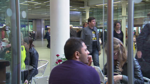 People sit at a cafe inside London's St. Pancras Station, UK.