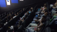 People sitting at the cinema watching a movie