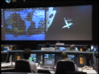 VIEW people sitting in Mission Control / MIR space station on screen in front of them / STS84