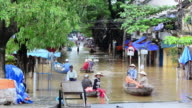 MS People sitting in water taxis and crossing flooded streets of Hoi An / Hoi An, Quang Nam, Viet Nam