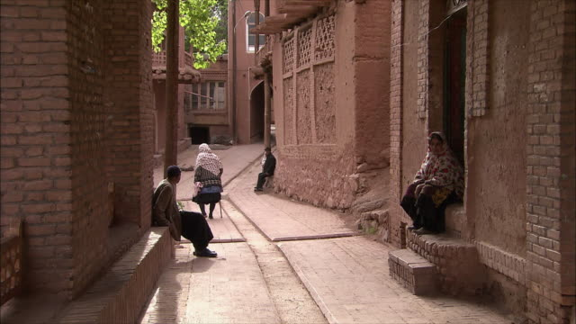 WS People sitting outside houses, woman walking down alley, Abyaneh, Iran