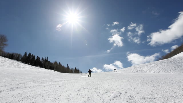 WS People skiing down ski run on blue sky day / Park City, Utah, United States