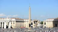 People stand at StPeter's Square during a hot summer day