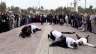 People stand in silence and a group stages a play to commemorate the victims of Halabja Massacre on its 27th anniversary at the Shanadar Park in...