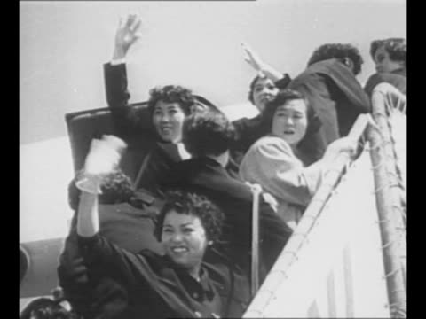 People stand on airfield wave airport building stands in background / montage Hiroshima Maidens wave as they board plane bound for the US where they...